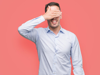 Handsome young businessman smiling and laughing with hand on face covering eyes for surprise. Blind concept.