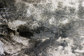 Textured detail on an old weathered concrete surface with contrasting light and dark areas and patterns of random shapes formed from the cracks.