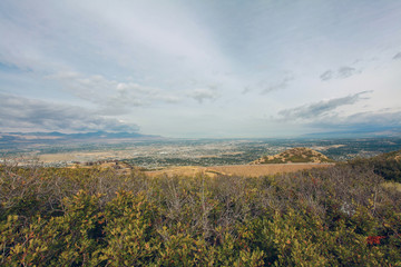Panoramic overview of the city valley. Fall grass and dry bushes upfront.