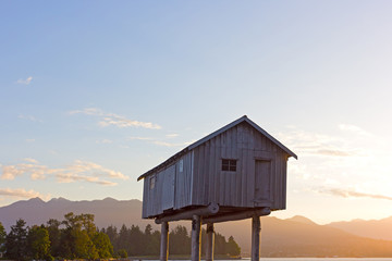 A witch shelter with slightly ajar door is standing in water at dawn in Vancouver harbor, BC, Canada. A raised wooden storehouse on wooden legs against forest and mountain chain.