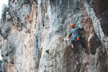 A man in helmet climbs the rock.