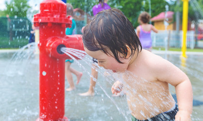 Happy toddler boy playing in water park spray ground
