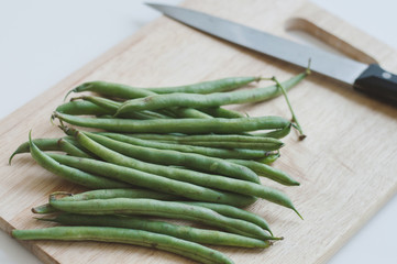Fresh raw green beans and a big knife on wooden cutting board. Food ingredient