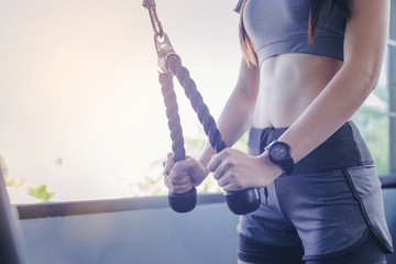 Close up of fit woman exercise with cable weight machine in gym.