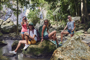 Young caucasian tourists sit on the rocks in the jungle by the river against the backdrop of the waterfall