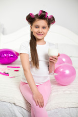 Adorable girl sitting on her bed holding glass of milk. Beautiful little lady sitting in sassy pose crosslegged at edge of bed holding wine glass with milk.