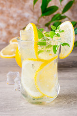 Refreshing cold mineral water with lemon, mint and ice cubes in glasses on a wooden table