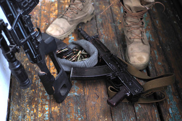 soldier feet and AK rifle on the floor close up.