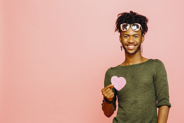 Portrait of a smiling young man holding a pink heart, isolated on pink studio background
