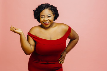 Portrait of a happy plus size woman in red dress, isolated on pink studio background
