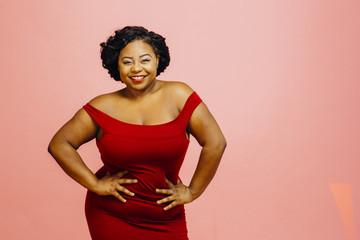 Portrait of a happy and confident plus size model in red dress