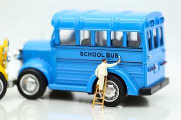 Miniature people: Workers brush painting school bus,Back to school concept.
