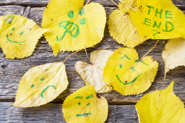 Yellow autumn leaves with smiley patterns on wooden background.