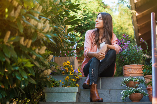 Relaxed young female smiling and looking side, sitting on home terrace. Hobby and resting leisure concept.