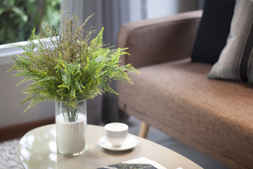 green plant vase on table and brown sofa in modern living room