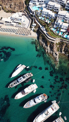 Aerial drone photo of luxury speed boats docked in popular beach of Psarou with iconic resorts, Mykonos island, Cyclades