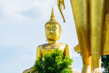 Big golden Buddha statue with blue sky background.