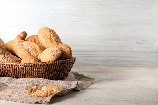 Wicker basket with fresh tasty bakery products on table