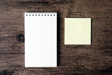 Top view image of blank notebook and empty sticky note paper on the wooden table..