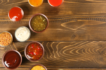 Bowls with different sauces on wooden background, top view