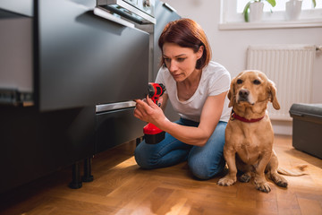 Woman with dog building kitchen and using a cordless drill