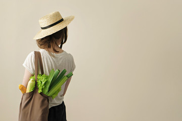 young woman holding textile grocery bag with vegetables
