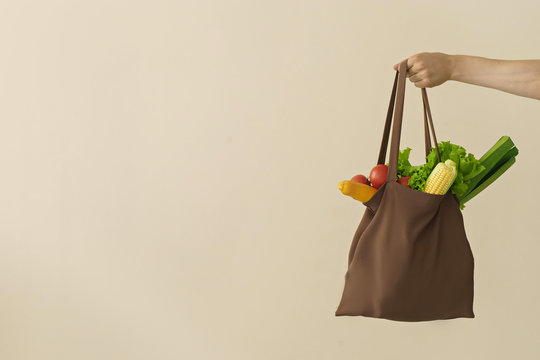 man hand holding cotton grocery bag with vegetables