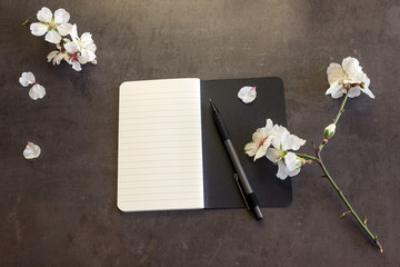 Notepad with pen and flowers of almond on a dark background. Copy space. Concept- diary keeping, creativity, business, spring mood.