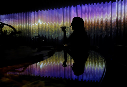 """A woman dines while the projection mapping is cast on table and walls during its media preview at """"TREE BY NAKED, yoyogi park"""" restaurant in Tokyo"""