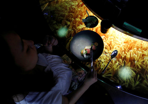 """A woman dines while the projection mapping is cast on a table during its media preview at """"TREE BY NAKED, yoyogi park"""" restaurant in Tokyo"""