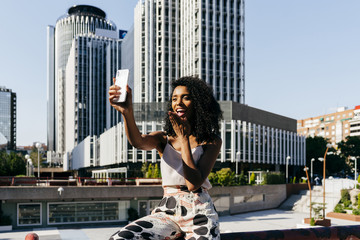 Cheerful black woman taking selfie on street