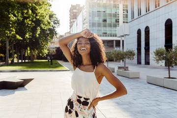 Cheerful black woman walking on street