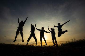 Silhouette of children jumping, happy and fun in the morning grassland, sunrise in nature.