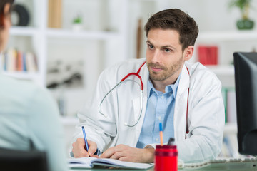 medical physician doctor listening to patient and taking notes