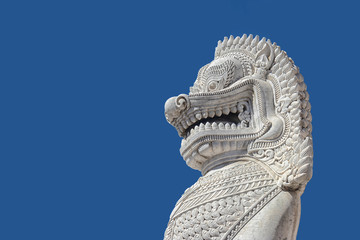 sculpture of ancient white stone singha statue isolated on blue sky background in front of temple in Bangkok, Thailand , Southeast Asia