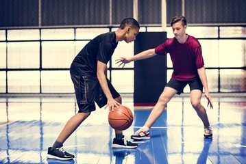 Two teenage boys playing basketball together on the court