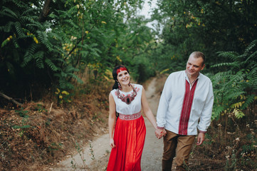 Ethnic wedding.A couple in national Ukrainian costumes walk in the forest among the trees.Man and woman walking and holding hands.A man in a Ukrainian shirt embroidered with ornaments. Ivana Kupala.