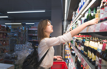 Attractive woman with a red basket in his hands takes beer from the supermarket counter. Woman chooses beer in the alcohol store of the supermarket department