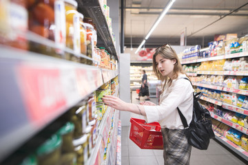 A stylish young woman with a red shopping basket in her hands selects canned vegetables in a supermarket. Attractive Girl buys canned vegetables in a supermarket