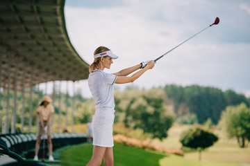 selective focus of female golfer in polo and cap playing golf at golf course