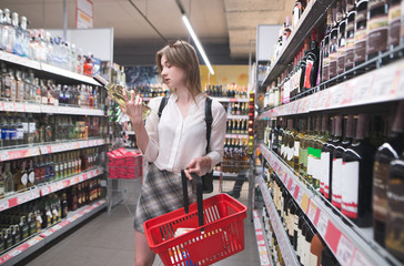 Cute woman with a blackcake for shopping in her hands chooses wine in the alcohol department of the supermarket. Girl looks at the wine bottle at the supermarket.