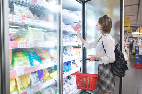 Stylish woman buys frozen food at a supermarket. Attractive young woman stands beside a freezer and chooses frozen foods. Purchase of products in a supermarket.