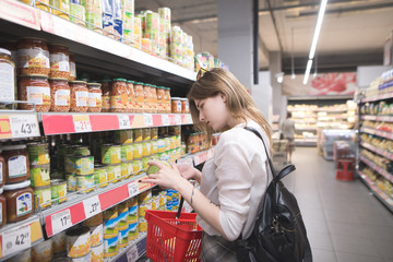 Stylish woman stands at the supermarket near the canned vegetable counter and looks at the cans in her hands. Girl chooses canned vegetables in the store. Purchase of products in a supermarket.