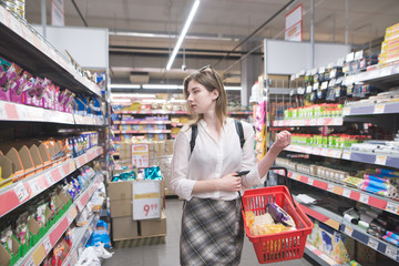 Portrait of a beautiful girl walking in a supermarket with a shopping cart in her arms and looking for products. Stylish young woman shopping in a supermarket.