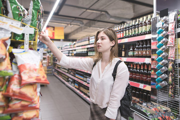 Portrait of a girl who buys chips in a supermarket. Woman chooses and buys the products in the store. Shopping in the supermarket
