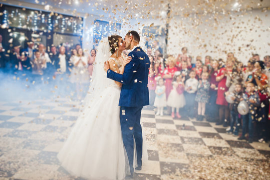 Gorgeous wedding couple performing their first dance with confetti, colorful lights and fireworks.