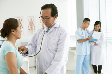 Doctor checking heartbeat of patient
