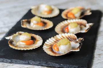 Galician style queen scallop dish, classic spanish tapas dish.selective focus.