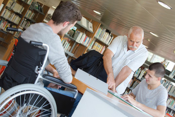 Man with students in library, one in wheelchair