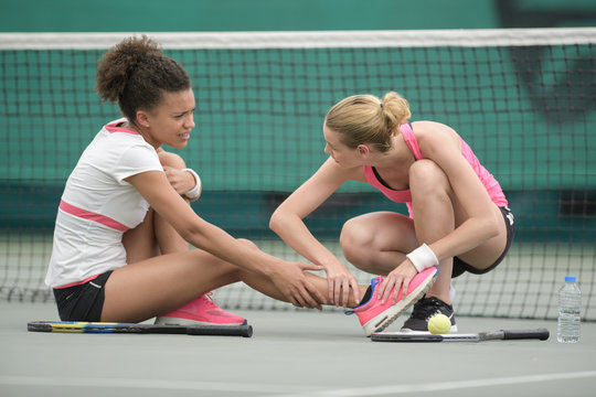 Lady helping fellow tennis player after injury